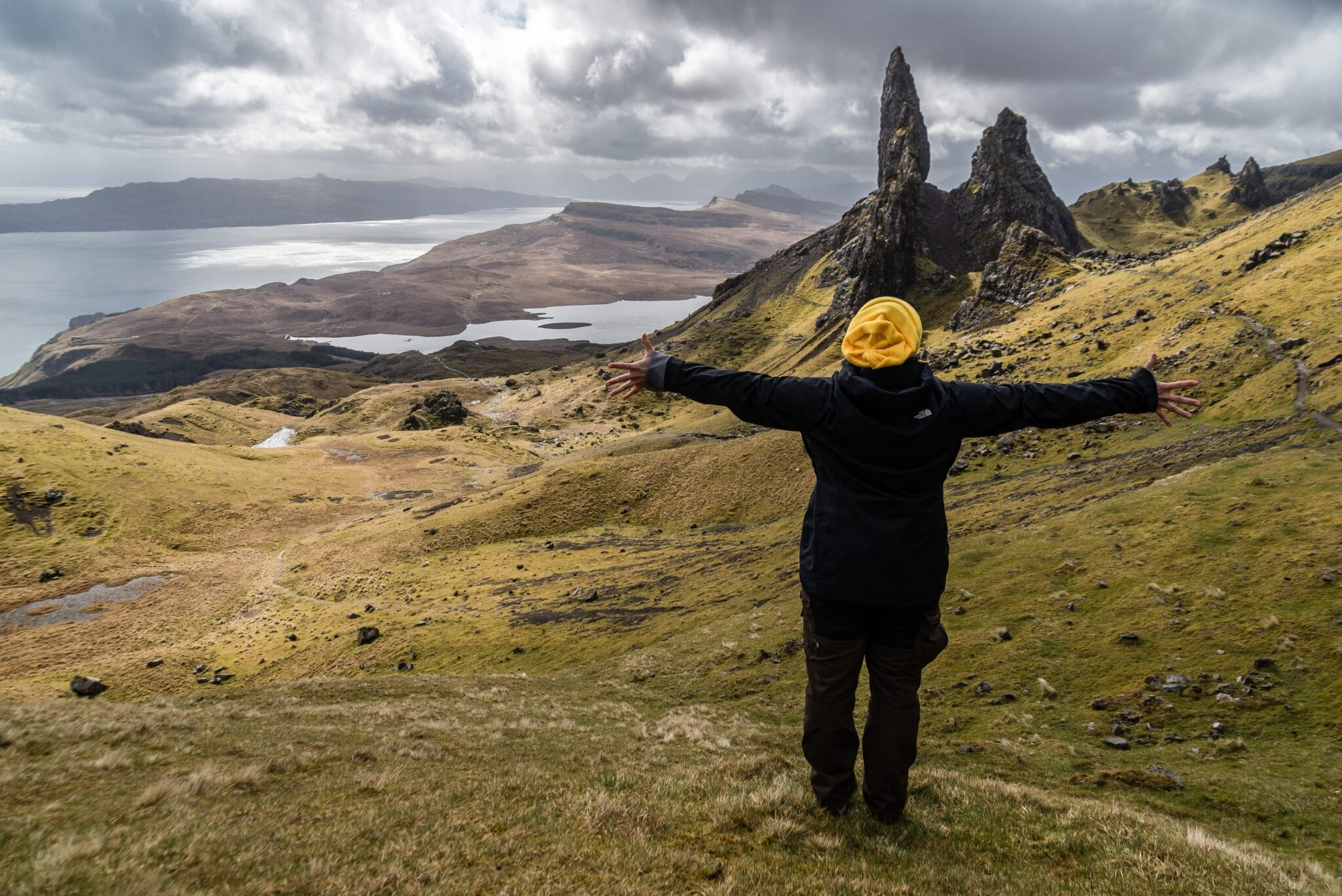A woam has spread her hands in front of Scottish scenery. Represents and idea of what to do .