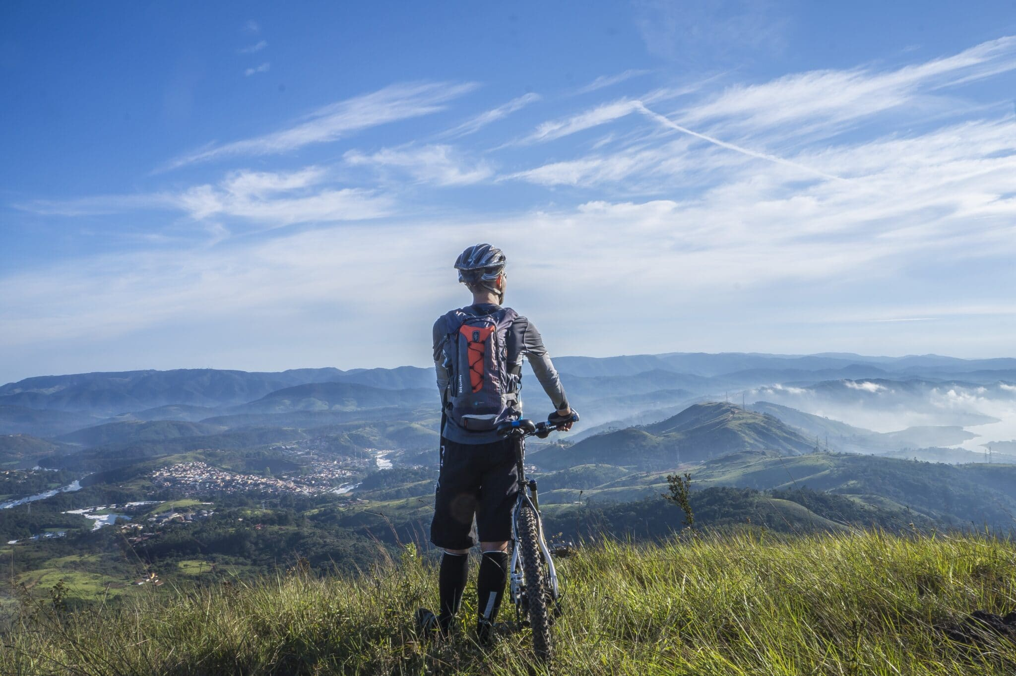 Cyclist looking at the view on top of a hill